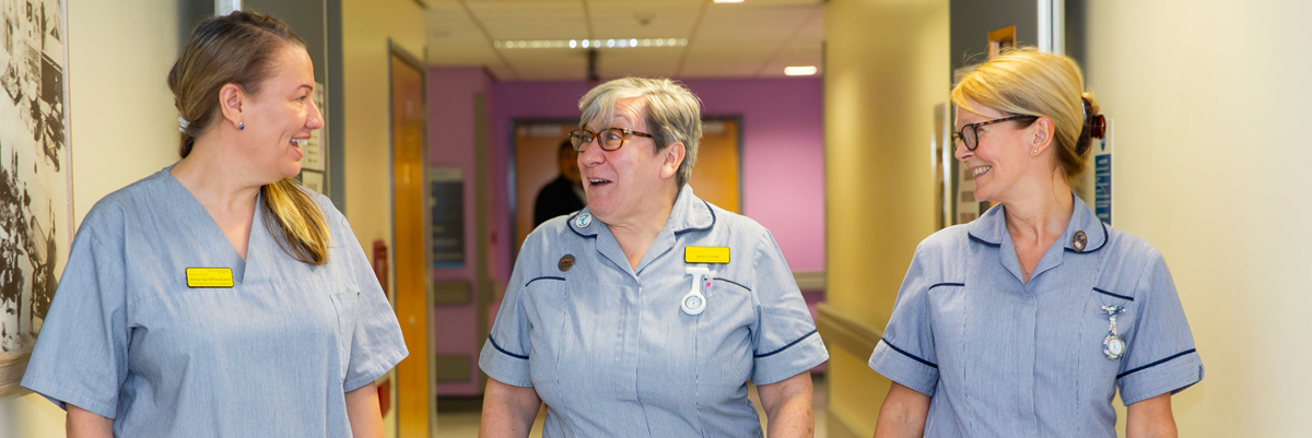 3 nurses in corridor laughing